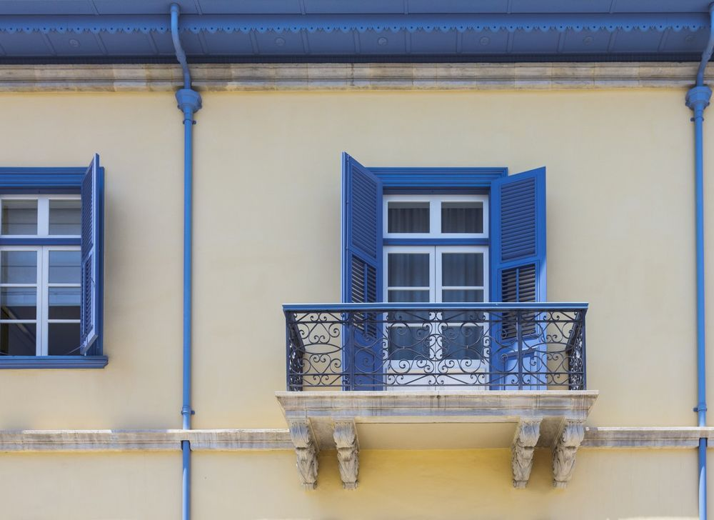 Te windows with opened blue shutters and balcony, Limassol, Cyprus